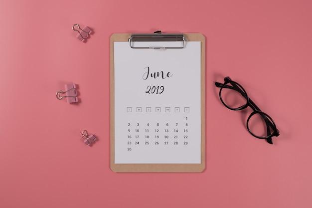 Calendrier laïque plat avec le presse-papier et lunettes sur fond rose. juin 2019. vue de dessus. Photo Premium