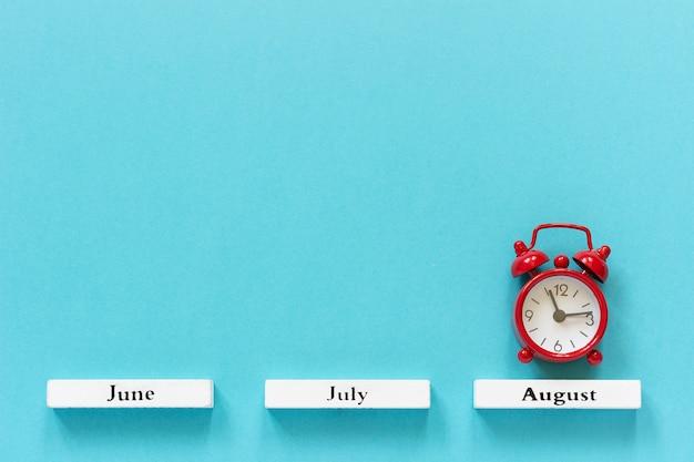 Calendrier mois d'été et réveil rouge au mois d'août sur bleu. concept août Photo Premium