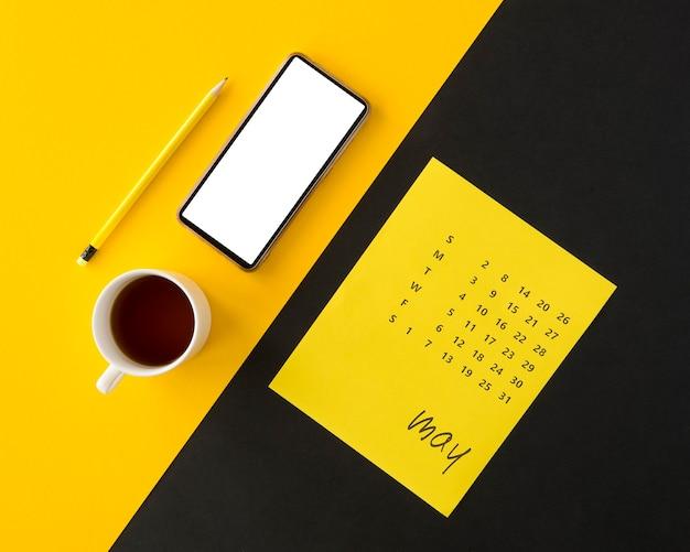 Calendrier De Planificateur Sur Fond Jaune Et Noir Avec Café Photo gratuit