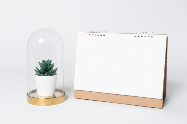 Calendrier en spirale de papier vierge et plantes dans un vase pour le modèle de la maquette Photo Premium