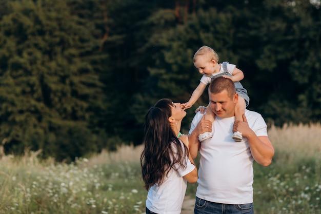 Des câlins chaleureux de jeunes parents et de leur petite fille debout dans le champ d'été Photo gratuit