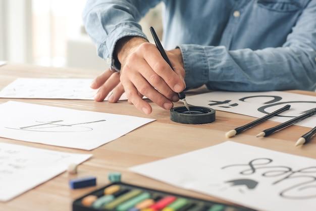 Calligraphiste Senior Masculin Travaillant Au Bureau Photo Premium