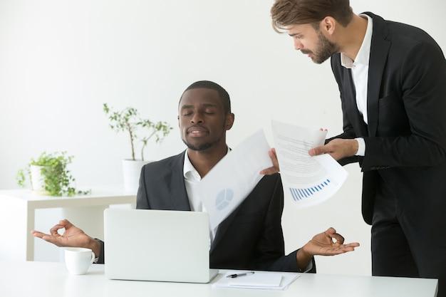 Calmer un homme d'affaires afro-américain pratiquant le yoga au travail en ignorant son patron en colère Photo gratuit