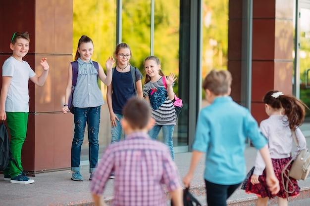 Les camarades de classe vont à l'école. les étudiants se saluent. Photo Premium