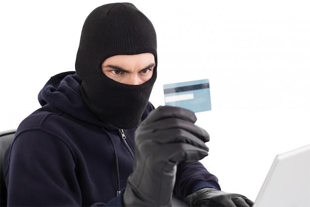 Cambrioleur utilisant une carte de crédit et un ordinateur portable Photo Premium