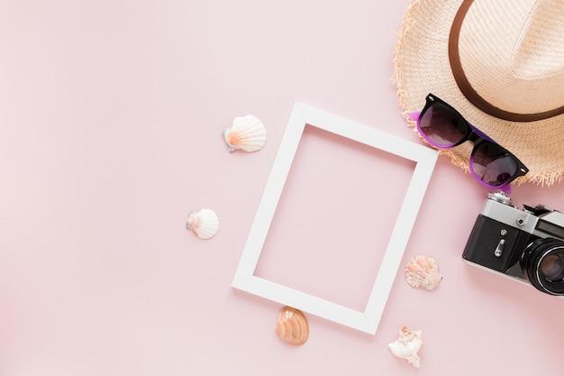 Caméra avec chapeau de paille, coquillages et cadre Photo gratuit
