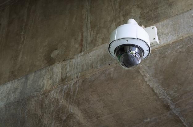 Caméra de surveillance circulaire blanche collée au mur de ciment. cctv. Photo Premium