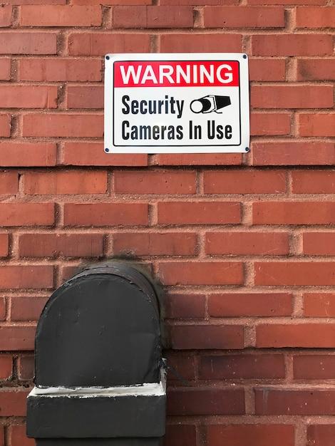 Les Caméras De Sécurité D'avertissement En Cours D'utilisation Signe Sur Un Mur De Briques Photo gratuit