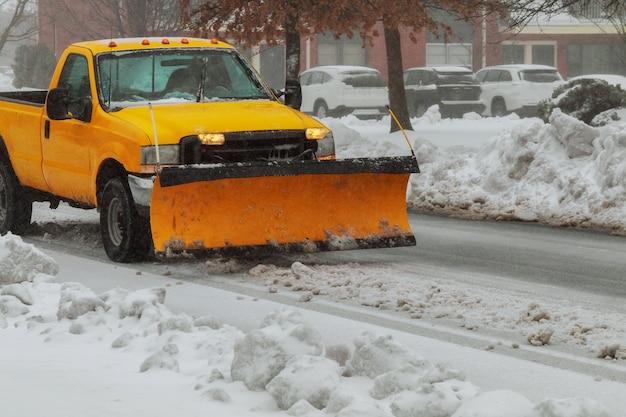 Un camion chasse-neige dégage une route après le blizzard de tempête de neige blanchi par blanc pour l'accès des véhicules Photo Premium