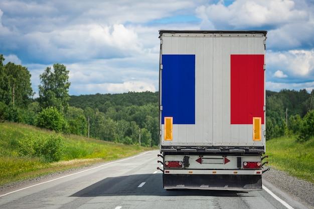 Un Camion Avec Le Drapeau National De La France Représenté Sur La Porte Arrière Transporte Des Marchandises Vers Un Autre Pays Le Long De L'autoroute. Photo Premium