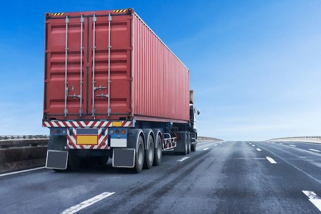 Camion sur la route de l'autoroute avec conteneur rouge, transport logistique sur l'autoroute asphaltée Photo Premium