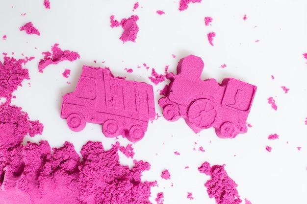 Camion et train réalisés avec un sable cinétique rose sur fond blanc. Photo Premium