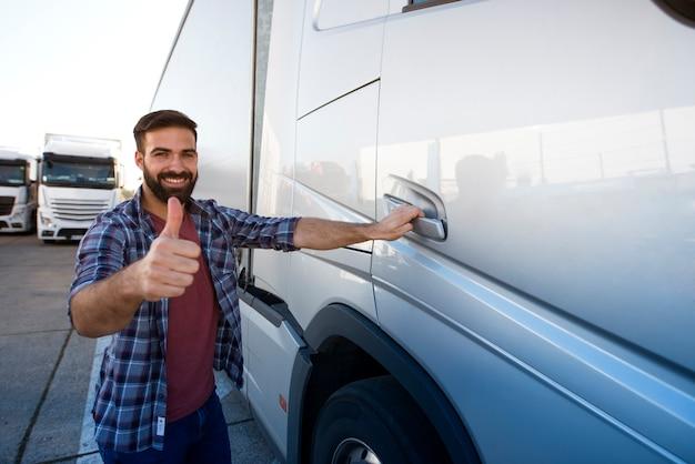 Camionneur Barbu Professionnel D'âge Moyen Debout Près De Son Camion Semi Et Tenant Les Pouces Vers Le Haut Photo gratuit
