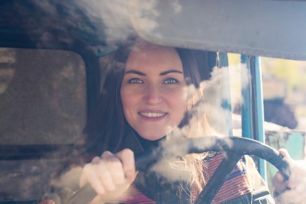 Camionneur dans la voiture. fille souriante à la caméra et tenant le volant. Photo Premium