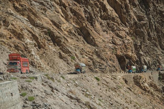 Des camions pakistanais circulant sur une route goudronnée le long de la montagne près de la falaise sur la route du karakoram. Photo Premium