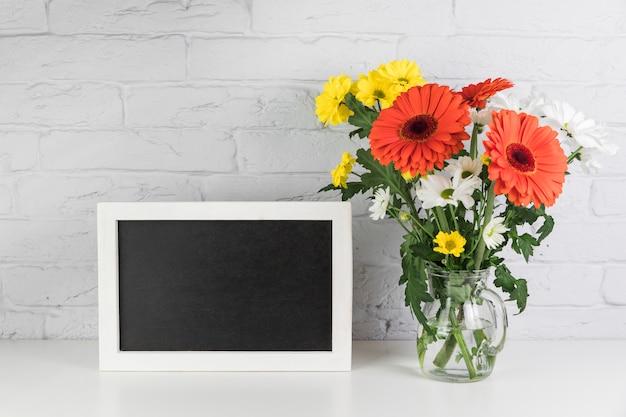 Camomille jaune et blanche avec des fleurs de gerbera rouge dans le vase près du cadre noir sur le bureau Photo gratuit