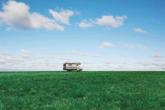 Camping-car Dans Le Champ Vert Sur Fond De Ciel Bleu Avec Des Nuages. Camping-car Sur La Nature. En Voyageant Photo Premium