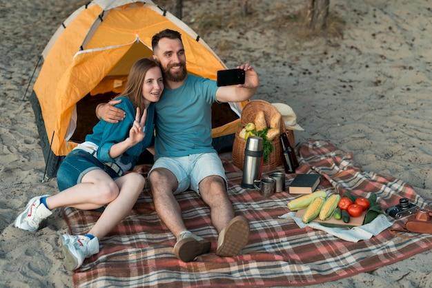Camping couple prenant un selfie Photo gratuit