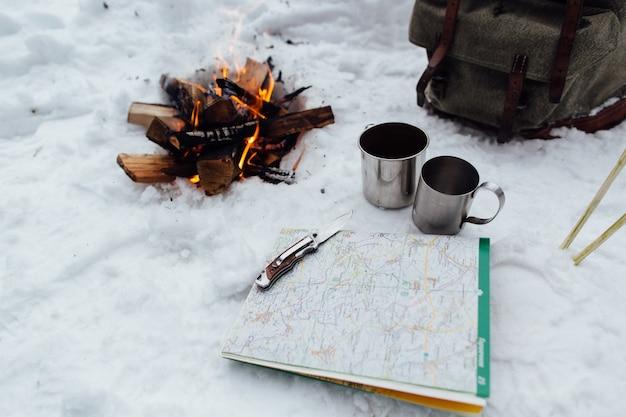 Camping. feu de joie avec deux tasses, carte et couteau sur la neige Photo gratuit