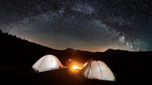 Camping De Nuit. Couple De Touristes Assis Et étreignant Devant Un Feu De Camp Près De Deux Tentes Illuminées Photo Premium