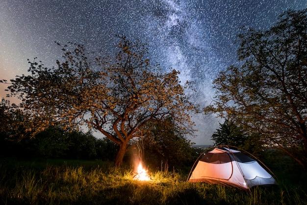 Camping de nuit. tente de touristes éclairée près du feu sous les arbres et ciel nocturne avec la lune Photo Premium