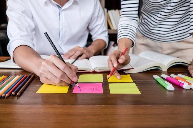 Le campus ou les camarades de classe des jeunes étudiants aident un ami à se familiariser avec son cahier de travail et à apprendre à faire du tutorat en se préparant à l'examen Photo Premium