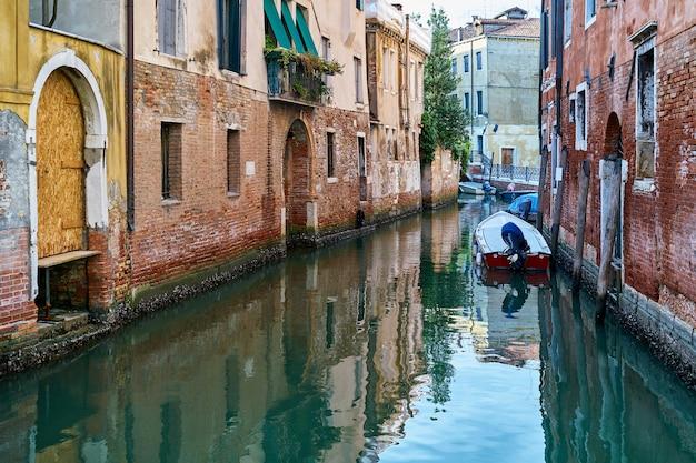 Canal étroit traditionnel avec des bateaux à venise, italie Photo Premium