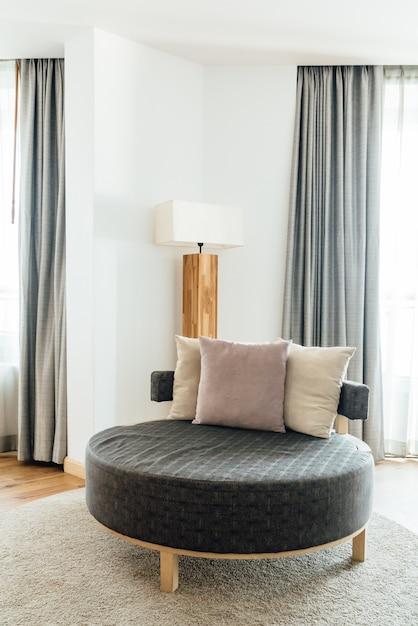 Canapé circle avec oreillers dans la chambre principale décorée dans des tons clairs et chaleureux. Photo Premium