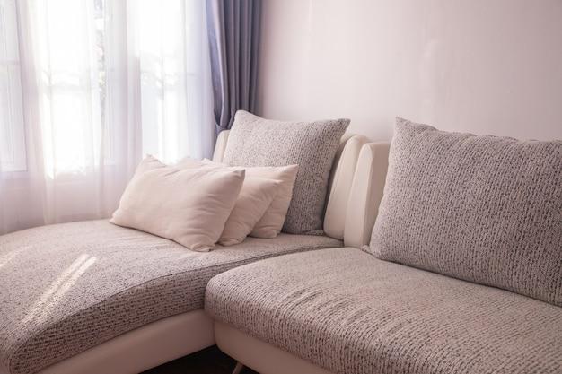 Canapé moderne dans le salon avec la lumière du soleil sur fond de rideau de fenêtres. Photo Premium