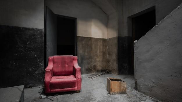 Canapé Rouge Dans Une Maison Sombre, Grise Et Abandonnée Photo Premium