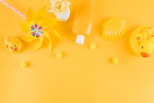 Canard en caoutchouc; moulinet; bouteille de lotion solaire; pétoncle avec petit pom pom sur fond jaune Photo gratuit