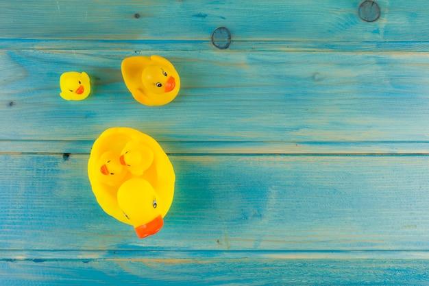 Canard Jaune En Caoutchouc Avec Canetons Sur Un Bureau Turquoise Photo gratuit