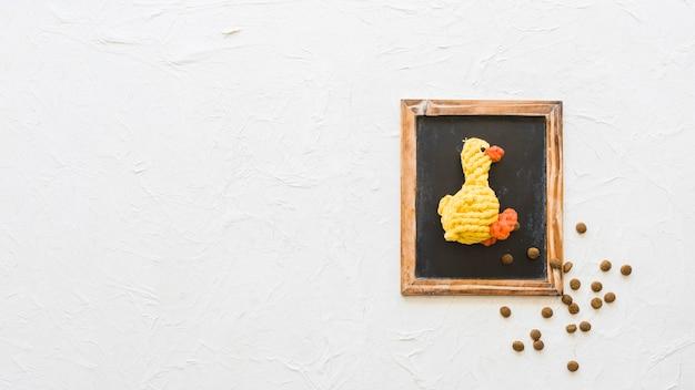 Canard Jouet Et Nourriture Pour Animaux De Compagnie Sur Tableau Noir Photo gratuit