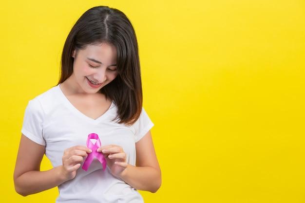 Cancer du sein, une femme en t-shirt blanc avec un ruban rose satiné sur la poitrine, symbole de la sensibilisation au cancer du sein Photo gratuit