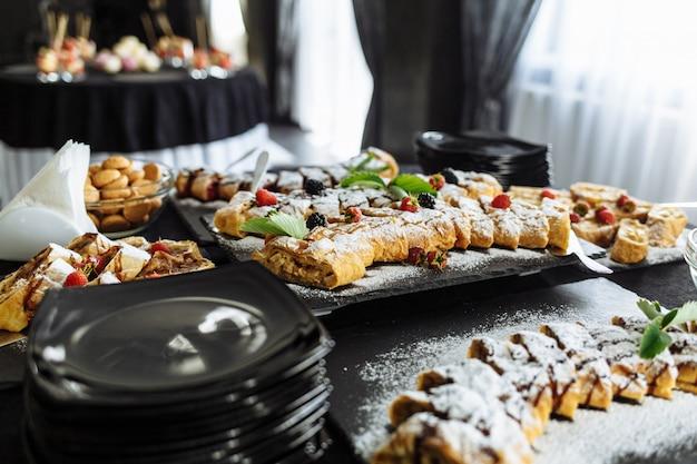 Candy Bar. Table Avec Différents Bonbons Pour La Fête. Table à Dessert Pour La Fête De Mariage. Décoré Délicieux. Bonbons, Bonbons, Desserts, Cupcakes, Tartelettes, Macarons, Gâteaux Et Muffins. Photo Premium