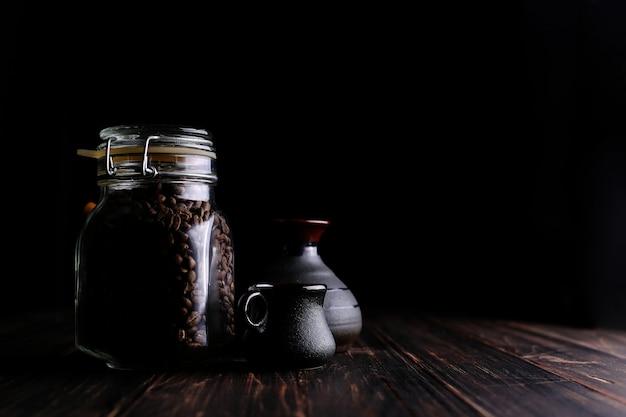 Une canette de café, une tasse et un turk sur une table en bois, sur un fond noir. Photo Premium