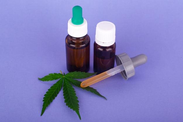 Cannabis Médical, Bouteilles Avec Teinture D'huile De Marijuana Sur Fond Bleu. Photo Premium