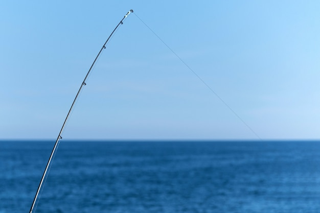 Canne à pêche contre l'océan bleu Photo Premium