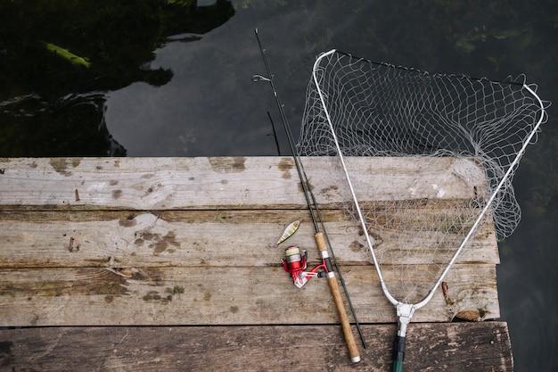 Canne à pêche et filet de pêche sur le bord de la jetée en bois Photo gratuit