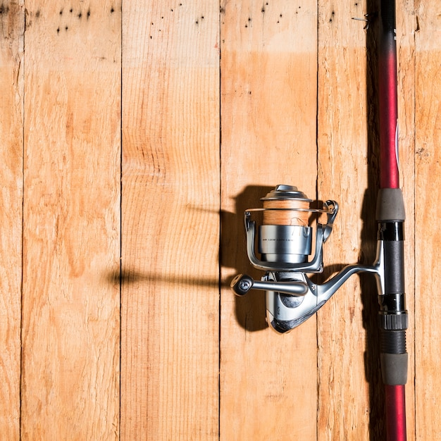 Canne à pêche avec moulinet sur un bureau en bois Photo gratuit