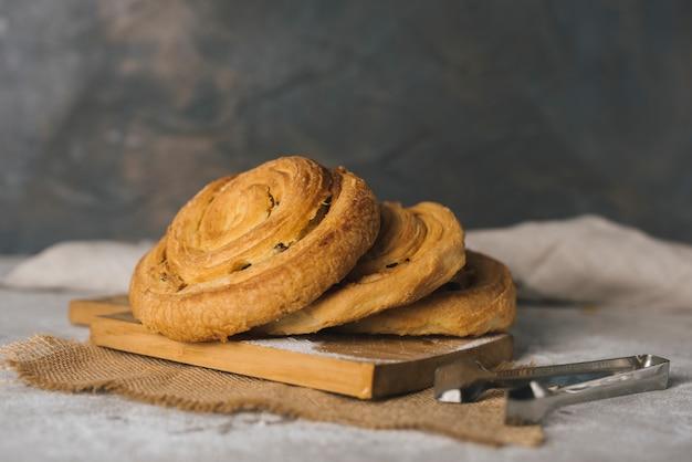 Cannelle fraîchement cuite roule des petits pains sur une planche à découper avec une pince Photo gratuit