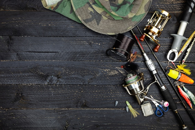 Cannes à pêche et moulinets, articles de pêche sur fond en bois noir Photo Premium