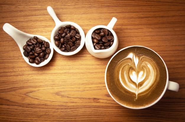 Cappuccino Chaud Avec Des Grains De Café Torréfiés Sur Une Surface En Bois Photo Premium