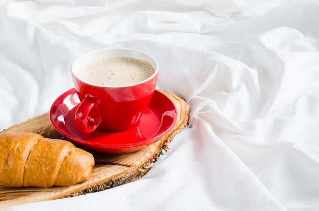 Cappuccino, chocolat et croissant sur un lit. Photo Premium