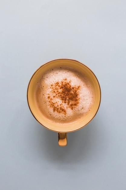 Cappuccino dans une tasse avec du chocolat en poudre sur fond blanc Photo gratuit