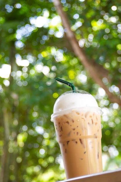 Cappuccino glacé dans une tasse en plastique. emporter paquet. boisson avec la nature verte bokeh backgr Photo Premium
