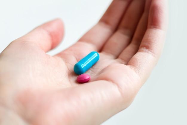 Capsule bleue et rose sur la paume de la femme sur fond blanc. pilules antidépresseurs dans une main féminine. Photo Premium