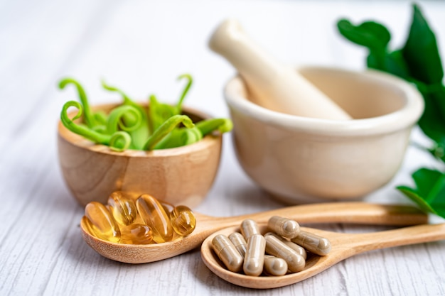 Capsule Organique à Base De Plantes De Médecine Alternative Avec De La Vitamine E, Huile De Poisson Oméga 3, Minérale, Médicament Avec Feuille D'herbes. Photo Premium