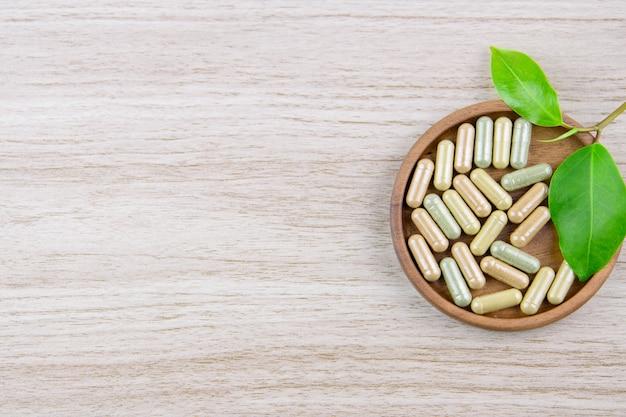 Capsule de vitamine dans la médecine à base de plantes bio de disque en bois de la nature Photo Premium