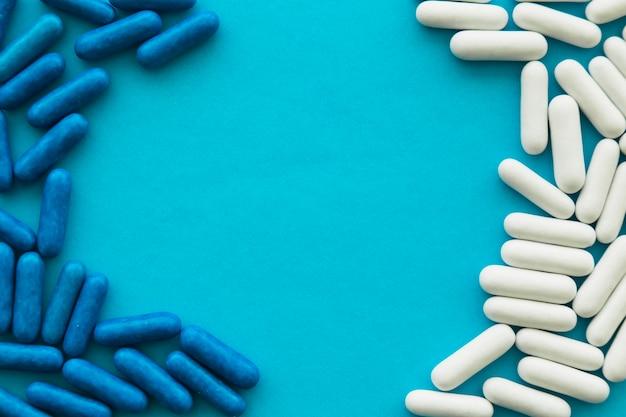 Capsules de bonbons blanc et bleu formant un cadre sur fond cyan Photo gratuit